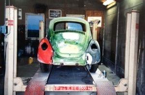 Oude gerestaureerde Volkswagen Kever op hefbrug tijdens beginjaren Autobedrijf Otten