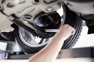 Een monteur die de onderkant van de auto inspecteert voor een APK keuring bij Autobedrijf Otten in Hoogeveen
