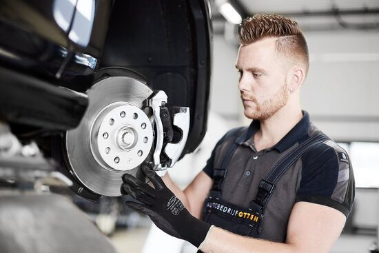 Een monteur werkt aan de remmen van een auto
